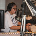 Rhonda Levaldo reads the news at KKFI studios